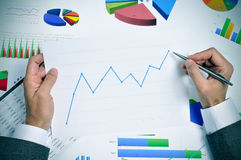 Businessman observing a chart with an upward trend. Businessman in his office desk full of graphs and charts observing a chart with an upward trend Stock Photo