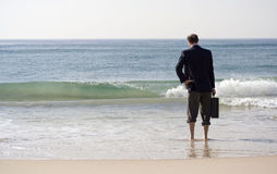 Businessman Ocean Break. Businessman in suit and holding a briefcase in his right hand, standing in the ocean surf with his pants rolled up to his knees, and his Royalty Free Stock Photos