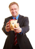 Businessman offerering piggy bank Royalty Free Stock Photos