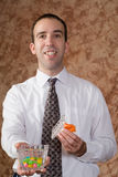 Businessman Offering Candy. A young businessman offering some candy from a glass dish royalty free stock photography