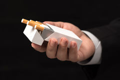Businessman Offering Cigarette Concept. With Dark Background royalty free stock photos