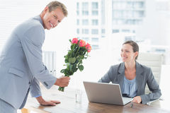 Businessman offering flowers to his colleague Royalty Free Stock Images