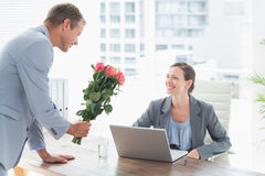 Businessman offering flowers to his colleague. In an office Royalty Free Stock Image