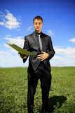 Businessman offering a folder. Man in black suit in the middle of the field Stock Images