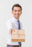 Businessman offering a gift box Stock Photography