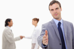Businessman offering hand with hand shaking colleagues behind hi Royalty Free Stock Photography