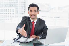 Businessman offering a handshake at office desk Stock Photo