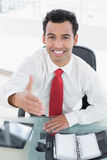 Businessman offering a handshake at office desk Royalty Free Stock Photo