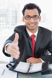 Businessman offering a handshake at office desk Stock Photography
