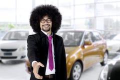 Businessman offering handshake in the showroom Stock Photos