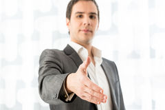 Businessman offering his hand in a handshake Stock Photos