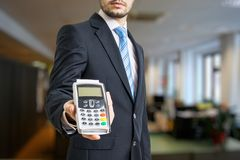Businessman is offering payment terminal for paying with credit card. Stock Image