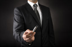 Businessman offering a pen Royalty Free Stock Images