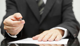 Businessman offering a pen to sign a contract Stock Photos