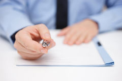 Businessman offering pen to sign Stock Photos
