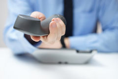 Businessman is offering telephone handset Royalty Free Stock Photo