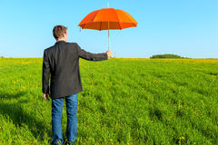 Businessman offering an umbrella Stock Photography