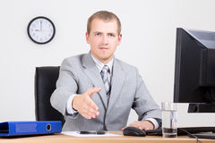Businessman offering a welcoming hand in office Royalty Free Stock Photos