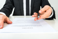 Businessman offering you to sign a document with focus to the te. Front view of a businessman offering you to sign a document with focus to the text Terms and stock photo