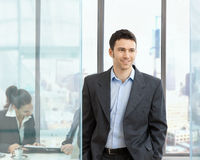 Businessman in office. Happy businessman standing in modern glass office, businesswoman sitting at desk in the background, looking at personal organizer stock images