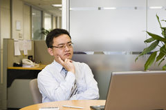 Businessman in office. Young asian businessman thinking hard for a solution Royalty Free Stock Photography