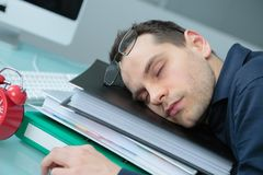 Businessman in office asleep on stack folders. Businessman in office asleep on stack of folders Royalty Free Stock Photography