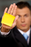 Businessman in office with blank adhesive note stuck to his hand Royalty Free Stock Photo
