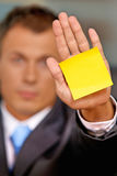 Businessman in office with blank adhesive note stuck to his hand Royalty Free Stock Image