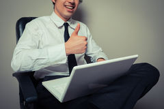 Businessman in office chair giving thumbs up. A young businessman is sitting in an office chair and is giving thumbs up Stock Image