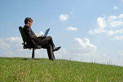 Businessman on office chair working with a laptop. Outdoor Royalty Free Stock Photos