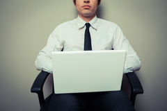 Businessman in office chair working on laptop. A young businessman is sitting in an office chair and is working on laptop computer Stock Photography