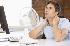Businessman in office with computer and fan