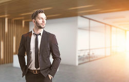 Businessman in an office corridor, toned. Portrait of a businessman with a beard. He is wearing a suit and standing with his hands in pockets. There is a Stock Photography