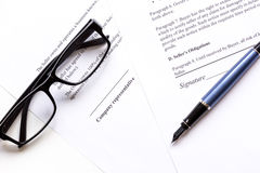 Businessman office desk with contract for signig, glasses and pen top view Royalty Free Stock Photography