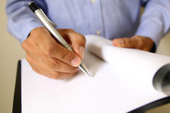 Businessman at office desk signing a contract Royalty Free Stock Photos