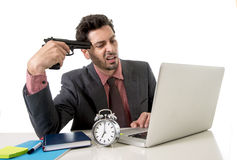 Businessman at office desk working on computer laptop pointing gun on his tempo in suicide gesture Royalty Free Stock Image