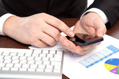 Businessman in the office with graphics holding a phone Stock Photo