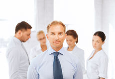 Businessman in office with group on the back Stock Images