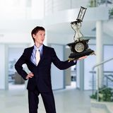 Businessman in office holding clock pyramid Stock Photo
