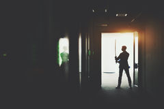 Businessman in office holding katana sword. Silhouette of boss or businessman in formal suit standing in dark office corridor interior with reflections and green Stock Photography