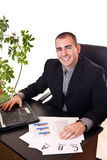 Businessman in office with laptop Stock Photography