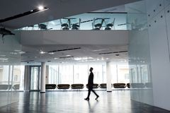 Businessman at Office Lobby. Profile view of confident businessman wearing suit walking along spacious office lobby with panoramic windows, motion shot Royalty Free Stock Photos