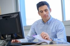 Businessman in office looking through catalogue Royalty Free Stock Image