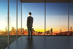 Businessman in the office looking over the city at sunset Stock Photography