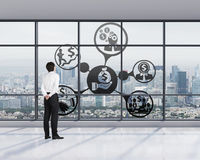 Businessman in office looking to business icons Stock Image