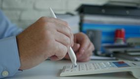 Businessman in Office Make Calculations Using Adding Machine and a Pen