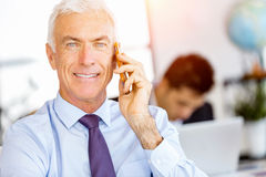 Businessman at the office with mobile phone Royalty Free Stock Photos