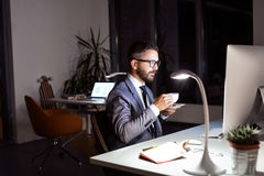 Businessman in the office at night drinking coffee. Royalty Free Stock Photos