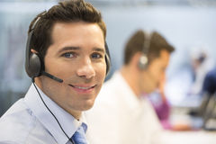Businessman in the office on the phone with headset, looking cam Stock Photography