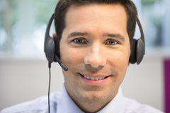 Businessman in the office on the phone with headset, looking cam Royalty Free Stock Photos